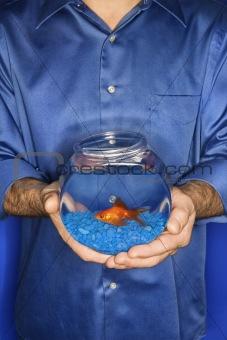 Man holding goldfish in bowl.