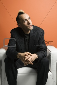 Caucasian man with mohawk wearing suit.