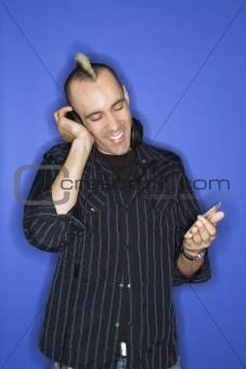 Caucasian man with mohawk listening to music.