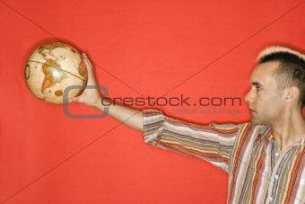 Caucasian man with mohawk holding globe.