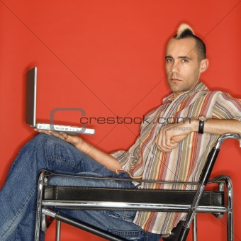 Caucasian man with mohawk with laptop.