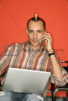 Caucasian man with mohawk using laptop talking on cellphone.