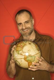 Caucasian man holding globe.