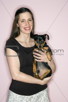 Caucasian woman holding Miniature Pinscher dog.