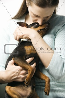 Caucasian woman and Miniature Pinscher dog.
