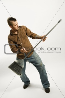 Caucasian man playing broom like guitar.