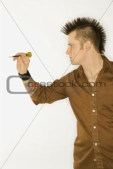 Caucasian man with mohawk throwing dart.