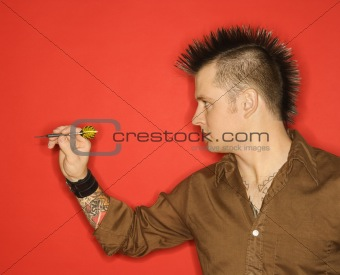 Caucasian man with mohawk throwing dart.