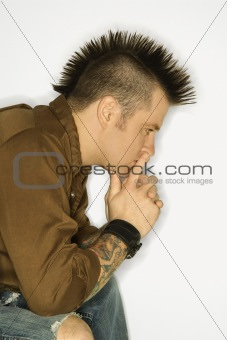Caucasian man with tattoos and mohawk.