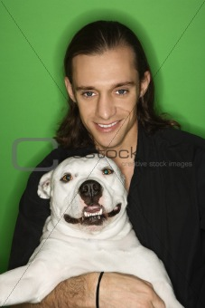 Caucasian young man holding white dog on lap.