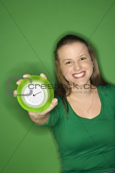 Caucasian young female adult holding out clock and smiling.