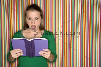 Caucasian female reading book making expression.