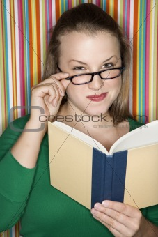 Caucasian female reading and looking at viewer over glasses.