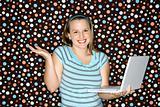 Young Caucasian woman holding laptop shrugging.
