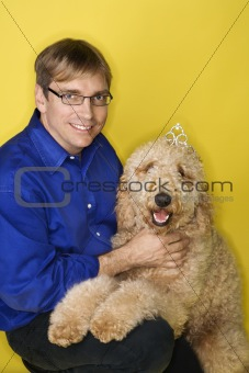 Caucasian man with Goldendoodle dog.