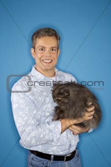 Caucasian man standing holding Persian cat.