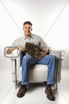 Caucasian man sitting holding Persian cat.