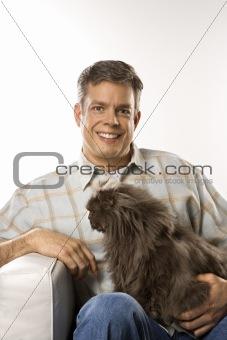 Caucasian man sitting holding Persian cat.