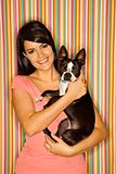 Caucasian woman holding Boston Terrier dog.