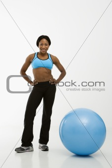 Woman standing with exercise ball.