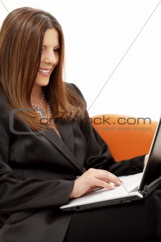 portrait of businesswoman with laptop in orange chair