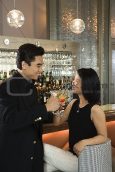 Attractive Man and Woman at Bar Having Cocktails
