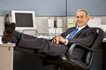 Businessman with feet up at desk