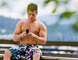 Man sitting on pier text messaging on cell phone