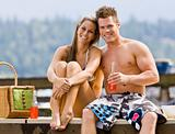 Couple sitting on pier drinking soda