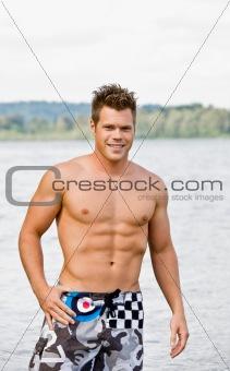 Man in swim trunks wading in lake