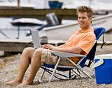 Man using laptop on beach