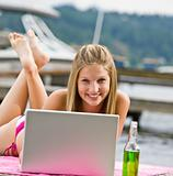 Woman laying on pier using laptop