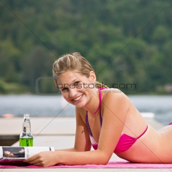 Woman laying on pier reading magazine
