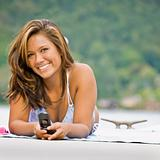 Woman laying on pier text messaging on cell phone