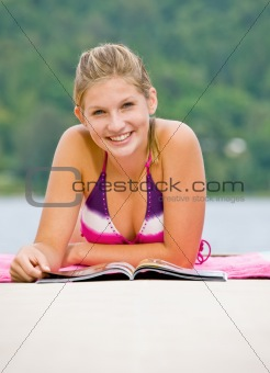 Woman laying on pier reading magazine