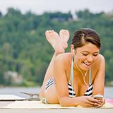 Woman laying on pier listening to mp3 player