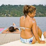Woman sitting on pier applying sunscreen lotion