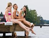 Friends sitting on pier at lake