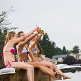 Friends sitting on pier at lake toasting with soda
