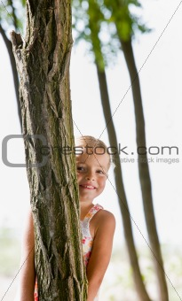Girl hiding behind tree