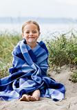 Girl wrapped in blanket at beach