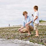 Father and son gathering rocks at beach