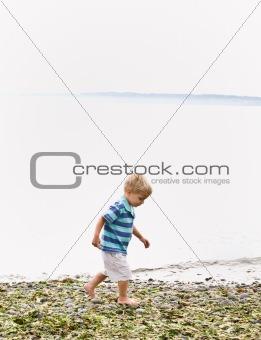 Boy walking near ocean at beach