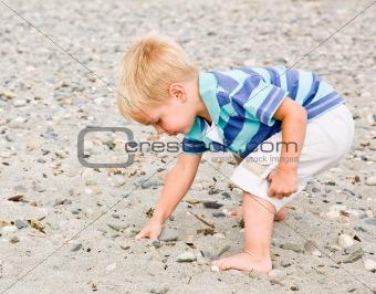 Boy gathering rocks at beach