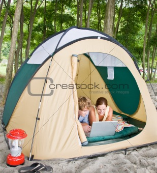 Couple in tent using laptop