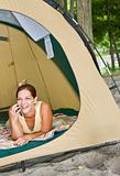 Woman laying in tent using cell phone