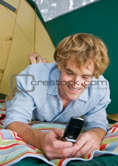Man in tent text messaging on cell phone
