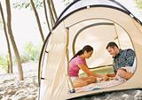 Couple playing boardgame in tent