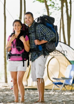 Couple carrying backpacks at campsite