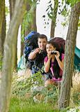 Couple with backpacks and binoculars outdoors